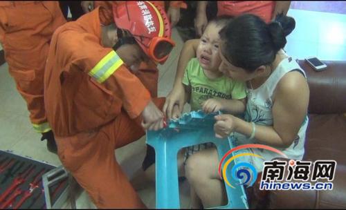 男孩的手指被塑料凳卡住,消防官兵正在施救。通讯员何宏国摄