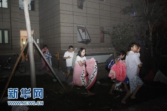 8月12日,天津滨海新区开发区发生剧烈爆炸后,市民涌向街边。当晚11时30分左右,天津滨海新区开发区发生剧烈爆炸,爆炸火光冲天,引发的烟尘高达数十米。 新华社发(总汇摄)