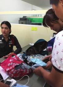 8月13日下午,芭提雅警察局,办案警官将张春蓉遗物交给其父母。 图/记者王欢