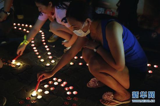 8月13日,在天津泰达第二小学安置点,天津市民为爆炸事故遇难者祈福。