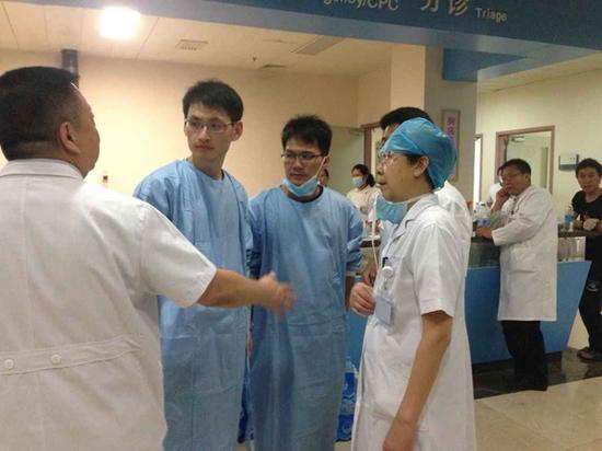 两名海南医生在救治间隙与当地医生交谈。(医院供图)