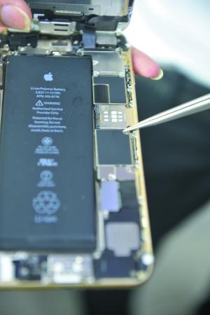 维修人员表示,苹果真机电池旁边的主板有黑色的贴膜。(信息时报记者 陈引 摄)