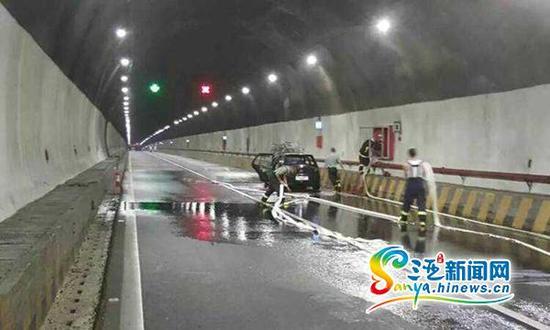 8月18日,G98环岛高速公路东线段三亚往海口方向大茅隧道内中间位置处一辆轿车发生自燃,消防官兵正在灭火。(图片由高速公路管理公司三亚站提供)
