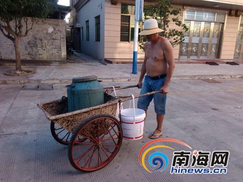 住户推着小车到附近借水。记者王渝摄