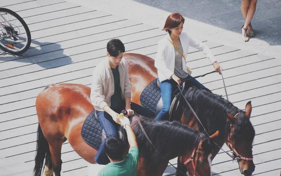 井柏然携陈意涵陌头骑马 谈笑自若引粉丝围观照相