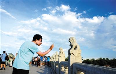 昨日,颐和园的游客在赏景拍照。当日,京城蓝天白云,空气质量达到优级,吸引众多游客。拍者 樊甲山