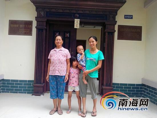 李昌女和女儿及家人在新居前(南海网记者刘培远摄)
