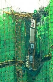 塔吊断裂后坠落在附近楼房的楼顶。刘陈平摄