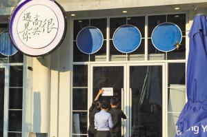 """昨天下午,餐厅工作人员在张贴""""暂停营业""""的通知。"""