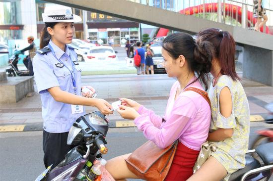 图为海口民警向市民发放交规教育卡。