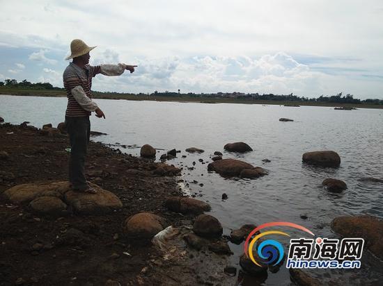 村民陈先生向记者介绍3名溺亡少年落水位置(南海网记者姜飞摄)
