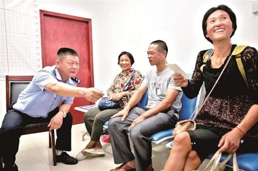图为:在民警的帮助下,流浪妇女(右一)与亲人相聚