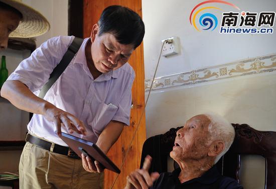 在文昌市抱罗镇抱罗村张修隆家里,邢峰在采访并做记录。