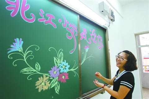 北江小学老师在黑板上写欢迎标语,欢迎新同学.图片