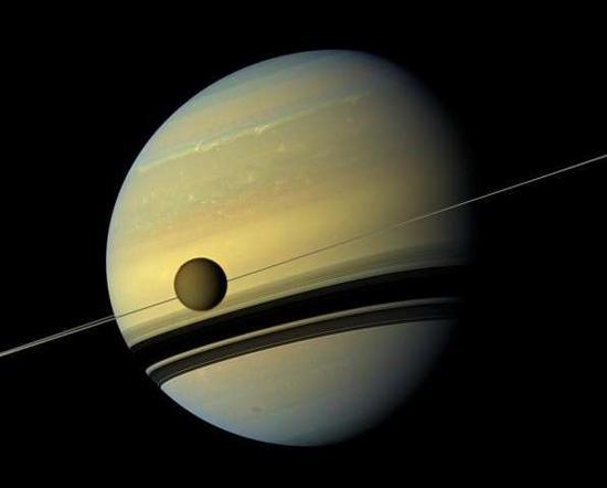 """美国宇航局""""卡西尼""""号飞船发回的彩色图片显示,巨大的土卫六绕行到巨大的土星正面。"""
