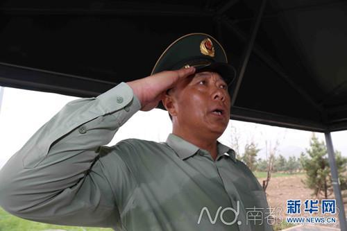 武警北京总队副司令员徐平正在进行敬礼动作,汗水已经湿透衣裳。