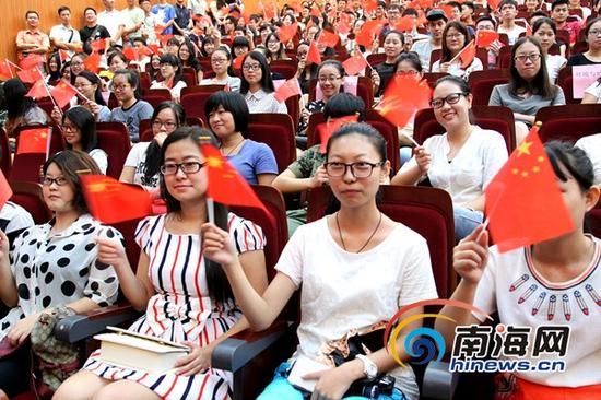 海南大学学生一边挥舞国旗,一边看纪念大会电视直播(南海网记者陈望摄)