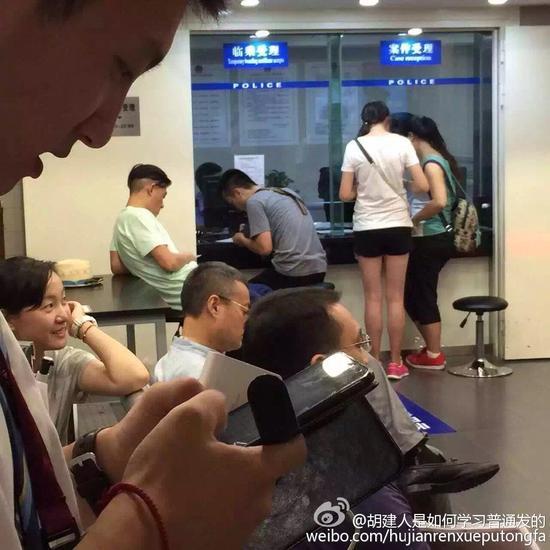 陈冠希淡定地靠在桌子上玩手机