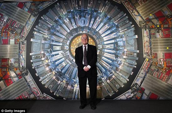 """在伦敦举行的""""科学博物馆对撞机展览""""期间,皮特·希格斯教授站在一幅大型强子对撞机的照片前。近日,利用这台世界上最强大的粒子对撞设备,科学家们大大加深了我们对于希格斯粒子的理解"""