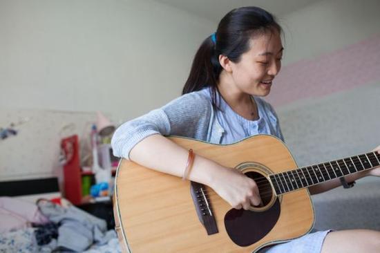 彭晓雯回家后弹着吉他唱起《宝贝》(9月7日摄)。
