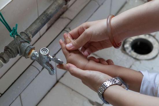 9月8日,彭晓雯为小朋友洗手。