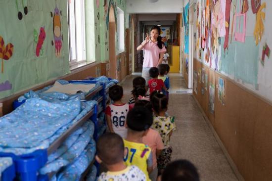 彭晓雯带着孩子们排队走向教室(9月7日摄)。