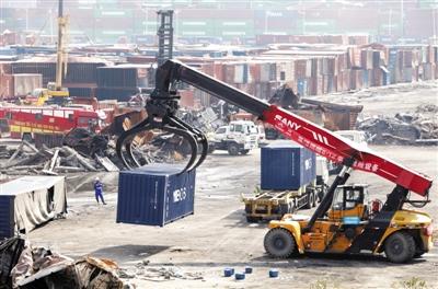 """9月8日,天津港集团施工人员正在清理""""三号山""""最后几个集装箱。目前,核心区集装箱已清理完毕。新华社发"""