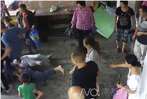 上前阻止的学校书记刘昌明摔倒后,打人家长的舅子还踹了他一脚。监控视频截图