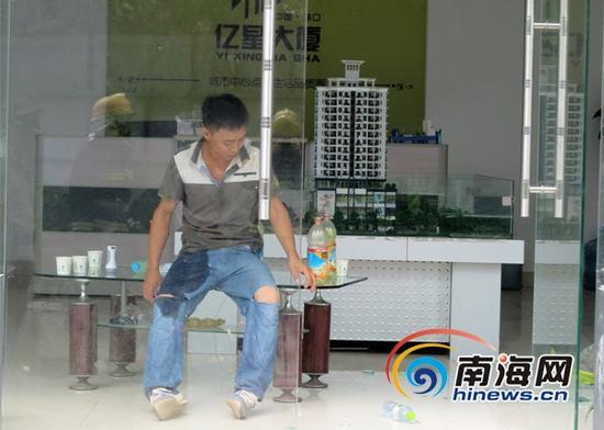 一年轻男子因劳资纠纷,坐在工地一层的售楼处里欲自焚。(通讯员吕书圣摄)