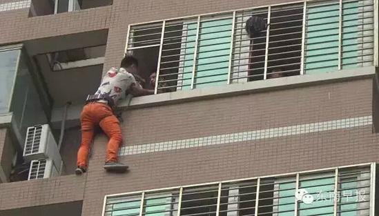男子挂在阳台外