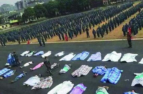 20多名女生裹着棉被躺在操场跑道上,接受太阳的照晒和两千余名同学的围观。(图片来源网络)