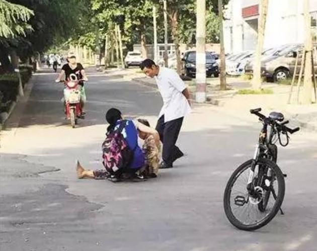 资料图:女大学生袁大宸扶着坐在马路中间的老太桂某。