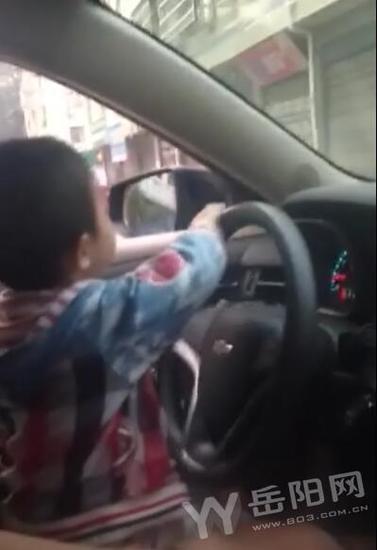 四五岁男孩开车穿行闹市
