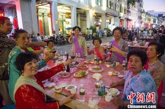 """市民和游客在海口骑楼老街体验""""长桌宴""""。 骆云飞 摄"""