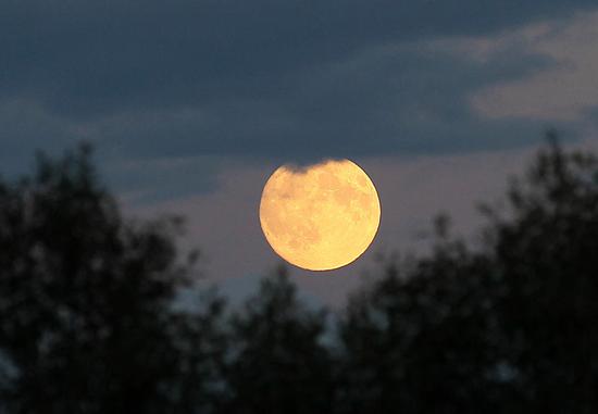 2015年9月27日,黑龙江双鸭山,16时50分,一轮明月在中俄边境乌苏里江畔俄罗斯境内天空悄然升起。