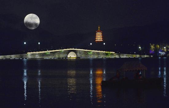 """2015年9月27日,游客在杭州西湖游船上欣赏中秋节的""""超级月亮""""。"""