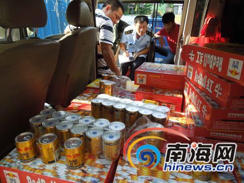 """琼山区食药监局执法人员正在对面包车上的假冒""""红牛""""饮料进行清点"""
