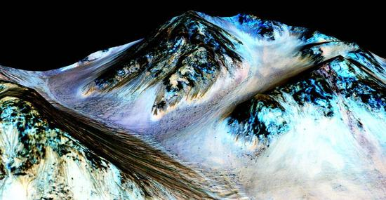 """这些深色、狭窄、100米长的条纹称为""""季节性斜坡纹线"""",从火星的陡峭山坡上延伸而下,科学家推断这是由同时期的流动水所形成的。近日,行星科学家在海尔火山口(Hale crater)探测到了水合盐,证实了最初的假说,即这些条纹确实是由于液态水流动而形成的。据推测,深色条纹上坡处的蓝色可能与其本身的化学组成无关,而是来自矿物质辉石的存在。该图片是由一张正射投影[红外-红-蓝/绿(IRB)]的假彩色图像(ESP_030570_1440)覆盖在一张同地点的数字地形模型(DTM)图像上制成的,后者是亚利桑那大学高分辨率影像实验(High Resolution Imaging Science Experiment,HiRISE)获取的影像。图像的垂直放大倍数是1.5。"""