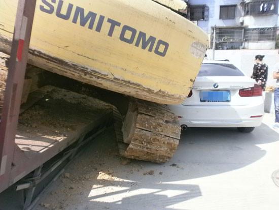 事故现场-平板车车轮陷进窨井 挖掘机从车上滑落砸中宝马