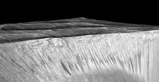 """狭小的深色条纹称为""""季节性斜坡纹线"""",从火星的Garni陨石坑外壁上发散而出。图中深色条纹长度可达数百米,据揣测是由于火星上含盐的液态水活动而构成。该图由一张正射投影[红外-红-蓝/绿(IRB)]的假黑色图像(ESP_030570_1440)笼罩在一张同地点的数字地形模子(DTM)图像上制成的,后者是亚利桑那大学高分辨率影像试验(High Resolution Imaging Science Experiment,HiRISE)获取的影像。图像的垂直缩小倍数是1.5。"""