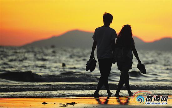 上图游客在三亚湾海边游玩。本报记者武威摄