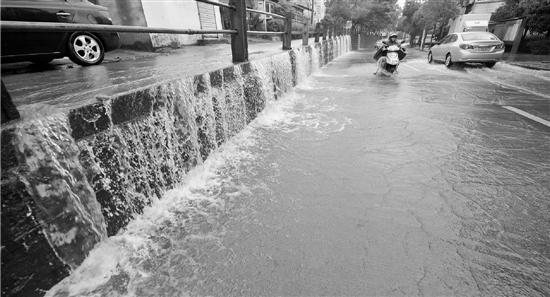 奉化城区河头路积水严重,高处积水如瀑布般。