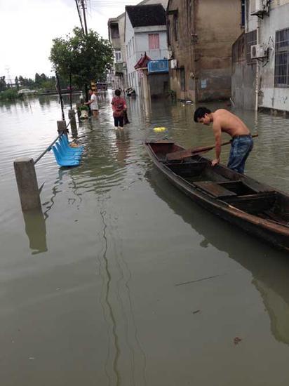 小丁正在用小木船护送村民和货物。 记者 吴震宁 摄