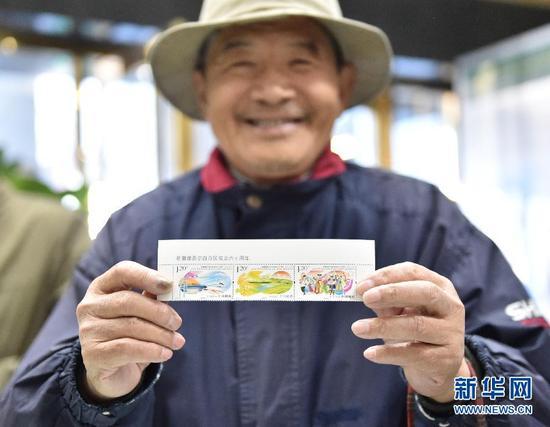 10月1日,在中國郵政北京西長安街支局內,一名市民展示剛買到的《新疆維吾爾自治區成立六十週年》紀念郵票。