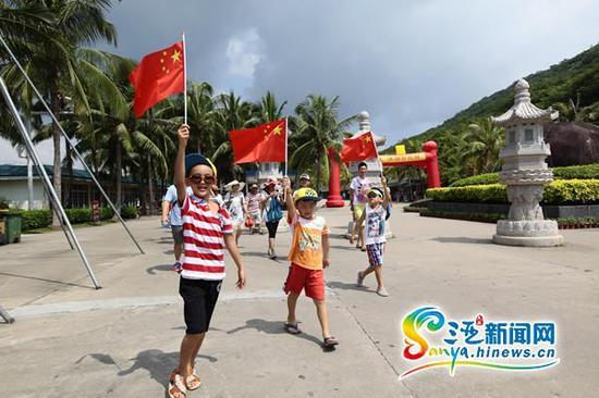 小朋友拿着五星红旗在三亚南山景区游玩。(通讯员陈文武摄)