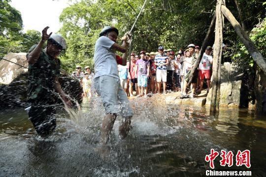 """10月2日,游客在海南呀诺达景区体验特色旅游项目""""踏瀑戏水""""。 曹传佳 摄"""