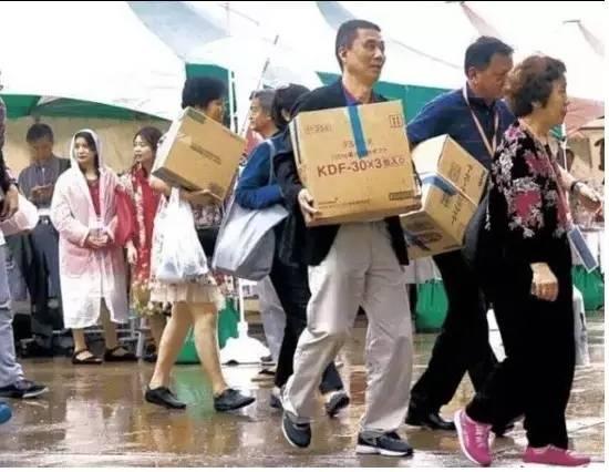 """雨中,中国游客购不停。一些日本百货店负责人表示:""""多亏了中国游客的到来,最近的生意越来越好了。"""""""