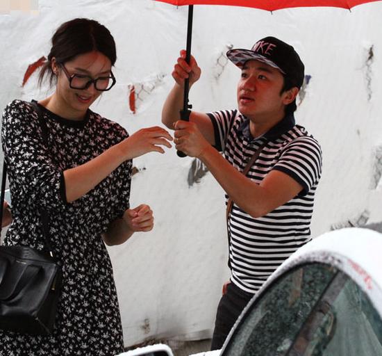 王祖蓝撑起巨伞,为李亚男挡雨
