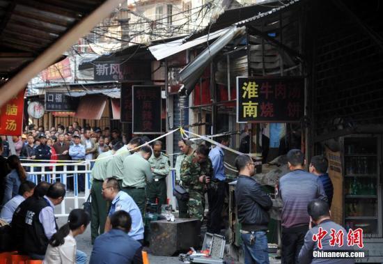 10月11日,芜湖杨家巷发生爆炸的店铺被封锁,现场消防、警察正在进行清理店铺等工作。中新社记者 韩苏原 摄