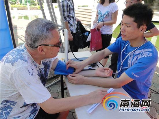 李冰为社区老人量血压(李冰原辅导员李咪提供)
